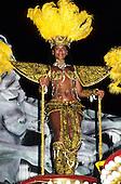 Rio de Janeiro, Brazil. Carnival; woman in ornate gold and black costume with feather headdress. Sapucai sambadrome.