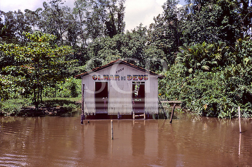 Amazon, Brazil. 'View of God'; small house on stilts just above the level of the water; near Belem.