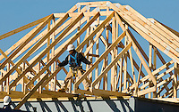 02/22/07:  A construction worker attaches a wooden rafter structure steel support beams during expansion/construction of a Charlotte-area shopping center. Charlotte, NC, is one of the country's fastest-growing cities. ..By Patrick Schneider- Patrick Schneider Photography.