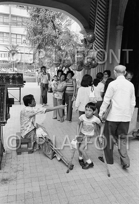 A handicapped boy sells lottery tickets on streets of Manila. Not having access to education, handicapped children and adults are forced work or beg on the streets.