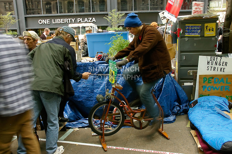 Man pedals bike to generate electricity for the Occupy Wall Street protest encampment at Zuccotti Park, in Lower Manhattan, October 22, 2001.