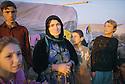 Irak 2000.Au camp de Talahi, cette femme, veuve,  revenue d'Iran, pose devant la tente ou elle vit avec ses enfants.Iraq 2000.A widow and her children in Talahi camp
