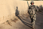 Shadows are cast on a mud wall as soldiers from Company D, 1st Battalion, 22nd Infantry head out on an early morning patrol in Malajat, near Kandahar, Afghanistan.  Oct. 4, 2010. DREW BROWN/STARS AND STRIPES