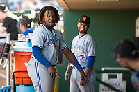 Surprise Saguaros Vladimir Guerrero Jr. (27) and position coach Andy Fermin (2), both of the Toronto Blue Jays organization, play a game in the dugout during an Arizona Fall League matchup against the Scottsdale Scorpions at Scottsdale Stadium on October 26, 2018 in Scottsdale, Arizona. Surprise defeated Scottsdale 3-1. (Zachary Lucy/Four Seam Images)