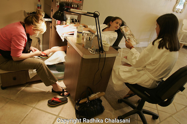 STUDIO CITY, CA-JUNE 10: Emily Andrews (120 (C) chats with a friend while having a pedicure and manicure during a spa party at Belle Visage Day Spa June 10, 2004 in Studio City. The spa hosts parties for 9-18 year-olds which cost between 87-119 USD per person. Cake, lunch and limo services are additional. With teens and pre-teens spending more and more money on health and beauty products a growing number of American spas are providing services to young people.(Photo by Radhika Chalasani)