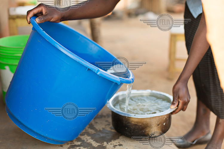 Mercy Chipeta (19) pours water, collected from a nearby river, into a pan to use for cooking.