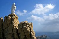 Notre Dame de la Serra statue perched on a rock above the city of Calvi, Corsica, France.