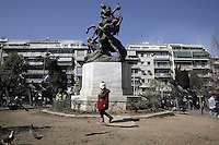 Pictured: A young migrant girl walks by a sculpture at Victoria Square Tuesday 23 February 2016<br /> Re: Refugees at Victoria Square in the centre of Athens, Greece