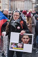 """Am Samstag den 31. Januar 2015 versammelten sich auf dem Staromestske Namesti-Platz (Alststaetter Markt / Old Town Square) in Prag ca. 500 Anhaenger der Pegida-Bewegung. Wie in Deutschland sind die Pegida (Patriotische Europaere gegen die Islamisierung des Abendlandes) Neonazis, Hooligans, Islamsfeinde und sog. """"Besorgte Buerger"""".<br /> Gegen die Pegida-Kundgebung protestierten Vertreter verschiedener Religionen, Antifaschisten, Sinti und Roma mit einem Gottesdienst, Gesaengen und Plakaten und Schildern, auf denen sich zum Teil ueber die Islamophobie der Pegida-Anhaenger lustig gemacht wurde. Beide Veranstaltungen fanden gleichzeitig nebeneinander auf dem Platz statt. Aus der Pegida-Kundgebung kamen immer wieder heftige Beschimpfungen und Neonazis versuchten Gegendemonstranten ein Transparent zu entreissen.<br /> Im Bild: Eine Pegida-Anhaengerin mit einem Schild auf das sie Fotos von Amnesty-International gegen die Folterstrafe gegen den saudiarabischen Blogger Raif Badawi geklebt hat. <br /> 31.1.2015, Prag<br /> Copyright: Christian-Ditsch.de<br /> [Inhaltsveraendernde Manipulation des Fotos nur nach ausdruecklicher Genehmigung des Fotografen. Vereinbarungen ueber Abtretung von Persoenlichkeitsrechten/Model Release der abgebildeten Person/Personen liegen nicht vor. NO MODEL RELEASE! Nur fuer Redaktionelle Zwecke. Don't publish without copyright Christian-Ditsch.de, Veroeffentlichung nur mit Fotografennennung, sowie gegen Honorar, MwSt. und Beleg. Konto: I N G - D i B a, IBAN DE58500105175400192269, BIC INGDDEFFXXX, Kontakt: post@christian-ditsch.de<br /> Bei der Bearbeitung der Dateiinformationen darf die Urheberkennzeichnung in den EXIF- und  IPTC-Daten nicht entfernt werden, diese sind in digitalen Medien nach §95c UrhG rechtlich geschuetzt. Der Urhebervermerk wird gemaess §13 UrhG verlangt.]"""