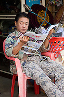 Myanmar, Burma.  Mandalay.  Burmese Man Reading Newspaper.