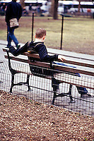 Young man sitting on park bench acting depressed<br />