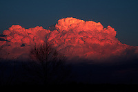 Cumulus congestus clouds are illuminated a vivid red-orange by the last rays of the sun just east of Norman Oklahoma in early March. Such clouds can be the precursor to thunderstorm activity.