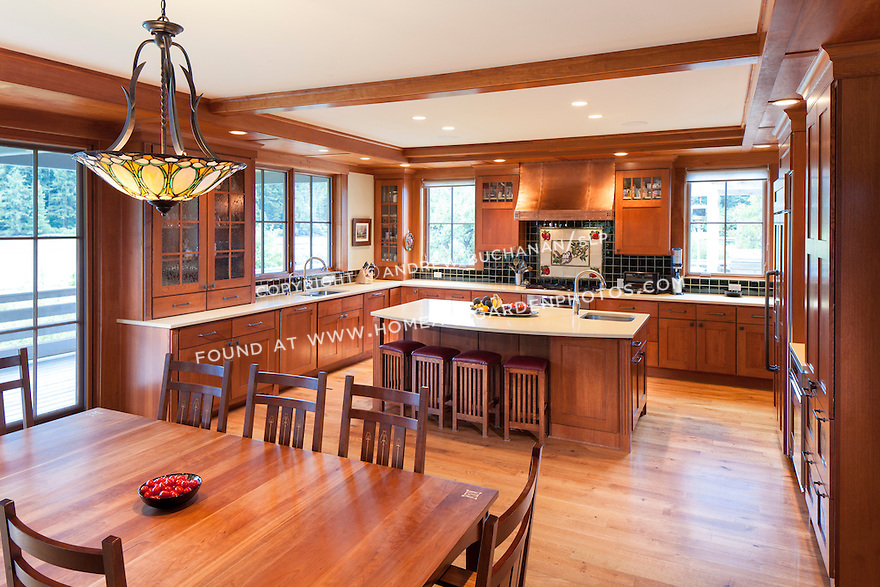 Decorative tile inset, copper range hood, and Tiffany chandelier are among the unique elements of this Craftsman style kitchen.