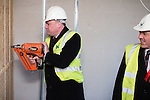 © Joel Goodman - 07973 332324 .  04/02/2014 . Manchester , UK . ED BALLS tries the nail gun as Mike Kane watches . Ed Balls , MP for Morley and Outwood and Shadow Chancellor of the Exchequer the Labour Party , joins Labour candidate Mike Kane on the campaign trail ahead of the Wythenshawe and Sale East by-election , following the death of MP Paul Goggins . They visit apprentices at the Leybrook Road building site in Wythenshawe where apprentice builders work on bungalows built for affordable rent . Photo credit : Joel Goodman
