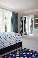 A guest room in blue and white has a light, fresh feel. A star pattern rug is repeated in the bed cover. A set of built-in mirrored wardrobes provides ample storage and gives a sense of space to the room.