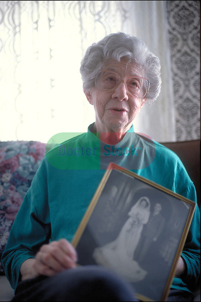 portrait of elderly woman sitting on living room couch holding photo of her wedding day