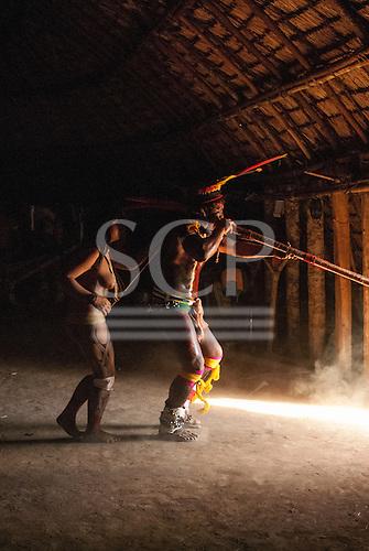 Xingu Indigenous Park, Mato Grosso, Brazil. Aldeia Matipu. Cacique's son Capuringa Kalapalo playing a sacred flute..