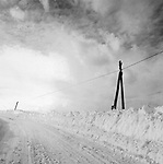 Scan of vintage print. Country road with snow and telephone pole and wire. Negative file #78-111. !978