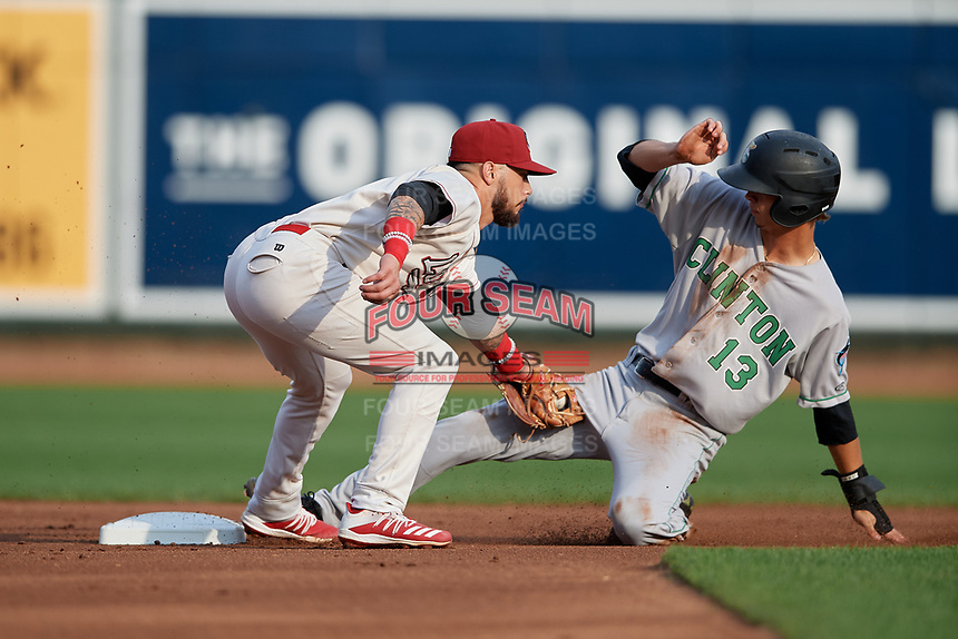 Great Lakes Loons second baseman Jacob Amaya (15) tags Connor Scott (13) sliding in during a Midwest League game against the Clinton LumberKings on July 19, 2019 at Dow Diamond in Midland, Michigan.  Clinton defeated Great Lakes 3-2.  (Mike Janes/Four Seam Images)