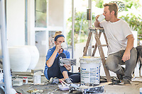 couple painting home together drinking coffee