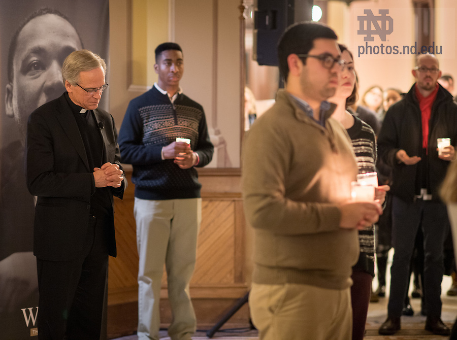 """January 15, 2018; Notre Dame President Rev. John I. Jenkins, C.S.C., listens during a candlelight prayer service in the Main Building in observation of Martin Luther King Jr. Day. The event also marked the beginning of """"Walk the Walk"""" week, a series of events and observances to celebrate and reflect on diversity and inclusiveness. (Photo by Barbara Johnston/University of Notre Dame)"""