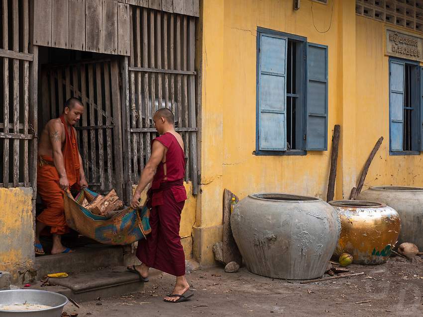 Buddhist Monks carrying firewood and piling it for storage to be used for fire wood in their kitchen for cooking, at an old Monastery in Battambang, Cambodia