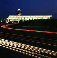 Dulles Airport in Northern Virginia at dusk. Car lights form trails in the foreground.