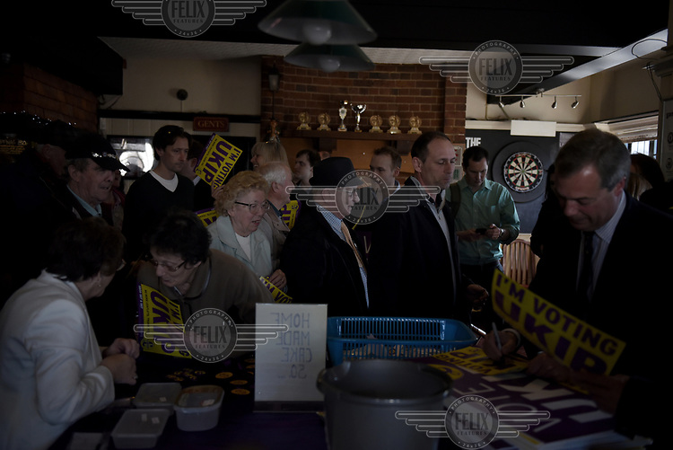 UKIP supporters queue up to collect their signed (by party leader Nigel Farage) window stickers and campaign materials following a public meeting in The Holly Tree pub in Margate, Kent during campaigning for the 7 May 2015 general election.