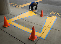 Fresh paint is rolled  onto concrete access ramps for the handicapped at a strip center mall.