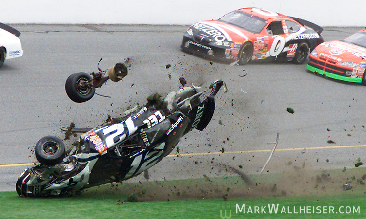 "Ryan Newman's #12 Alltel Dodge disintegrates as he crashes near the start-finish line during running of the Daytona 500 at the Daytona International Speedway in Daytona Beach, Florida February 16, 2003. Forty three drivers are competing in the 45th running of the ""Great American Race."" Jack Sprague's #0 NetZero Pontiac passes above along with the #19 Dodge Dealers Dodge driven by Jeremy Mayfield."
