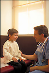 smiling doctor examining smiling young boy patient