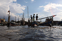 Indonesian children stand on fishing boats in the port area of northern Jakarta.<br />