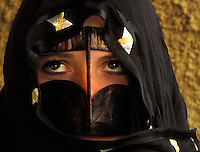 A young Middle Eastern woman in tradition Arab mask and dress.