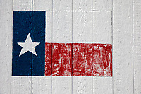Faded and rustic Texas flag painted on the side of a building.