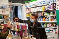 un farmacista con maschera protettiva e pannelli di plexiglass serve un cliente a distanza   a pharmacist with a protective mask and plexiglass panels serves a customer