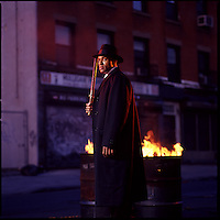 Man with night stick standing next to flaming trashcans