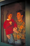 father holding child in doorway