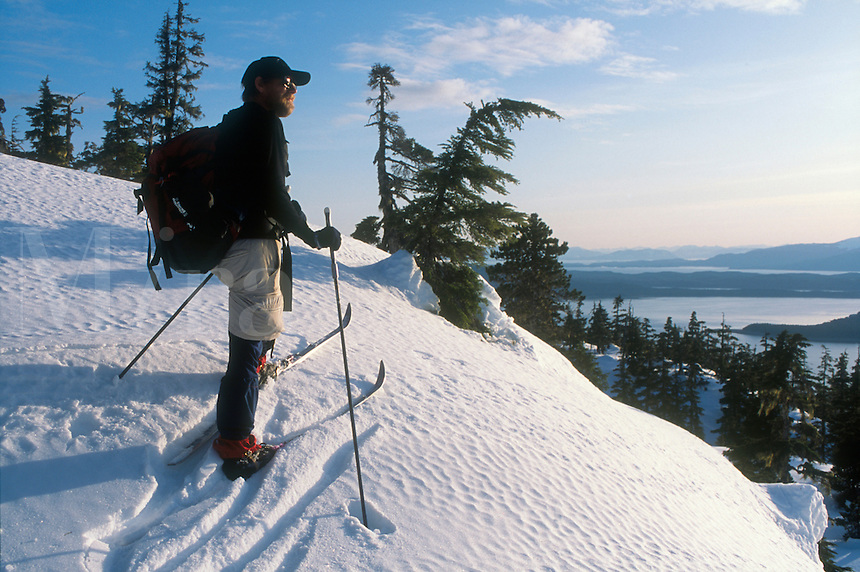 Man looks out of the archipelago of southeast Alaska from Auke Mountain near Juneau.  MR