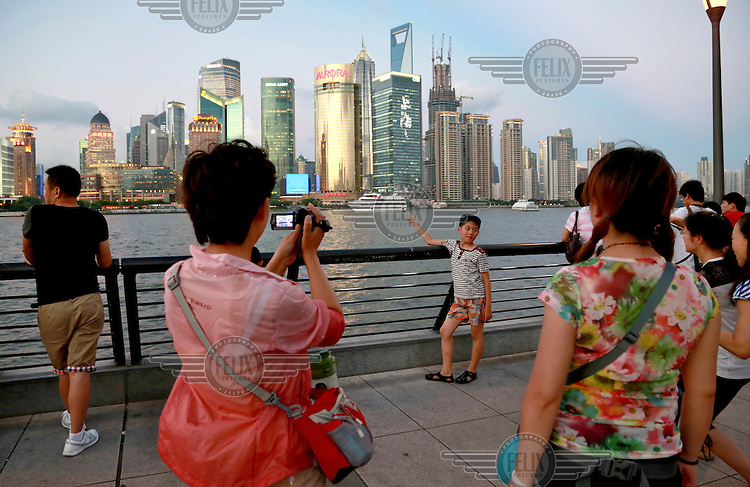 Tourists have their pictures taken while standing on the Bund. Once a river front that housed many foreign banks and bonded warehouses, the Bund, along with the skyscrapers of Pudong across the Huangpu river, has become the most recognizable icon for the city and the top tourist destination for Shanghai.