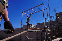 Construction workers wearing personal protective equipment - helmet, glove, uniform - occupational safety and health - iron and reinforced concrete. Sao Paulo, Brazil.