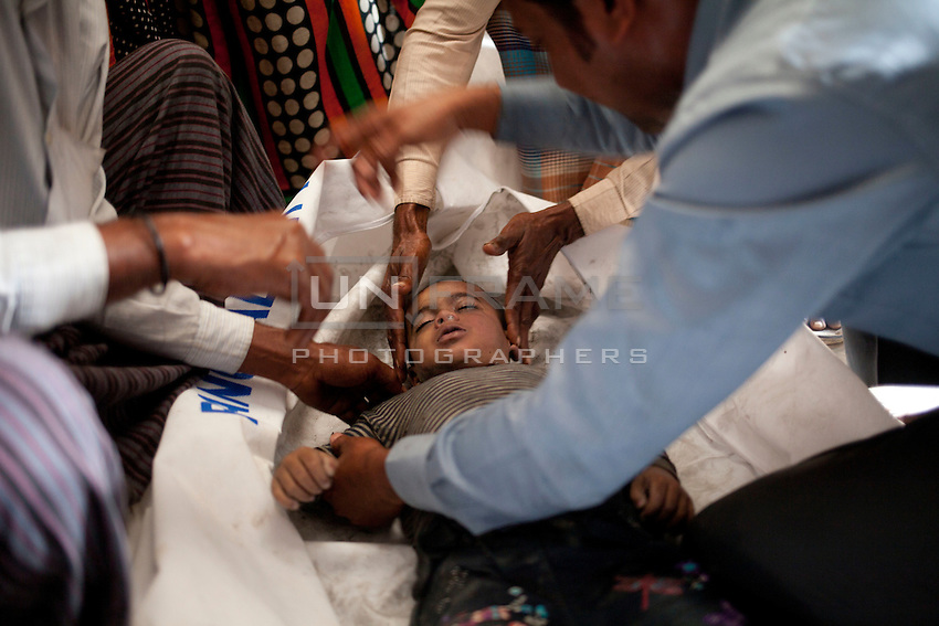 Bangladeshi relatives identifies the corpses of the victims - most of them children -  after a river ferry carrying more than 100 passengers capsized in the River Padma Sunday after being hit by a cargo vessel at Paturia, in Manikganj district, about 80 kilometers  northwest of Dhaka, Bangladesh. Feb. 22, 2015