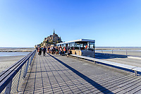 France, Manche, Mont Saint Michel bay, listed as World Heritage by UNESCO, The Mont-Saint Michel, bridge of the architect Dietmar Feichtinger and group of people boarding a shuttle // France, Manche (50), Baie du Mont Saint-Michel, classée Patrimoine Mondial de l'UNESCO, passerelle de l'architecte Dietmar Feichtinger et groupe de personnes montant dans une navettes