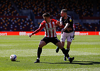 17th April 2021; Brentford Community Stadium, London, England; English Football League Championship Football, Brentford FC versus Millwall; Sergi Canos of Brentford is challenged by Scott Malone of Millwall