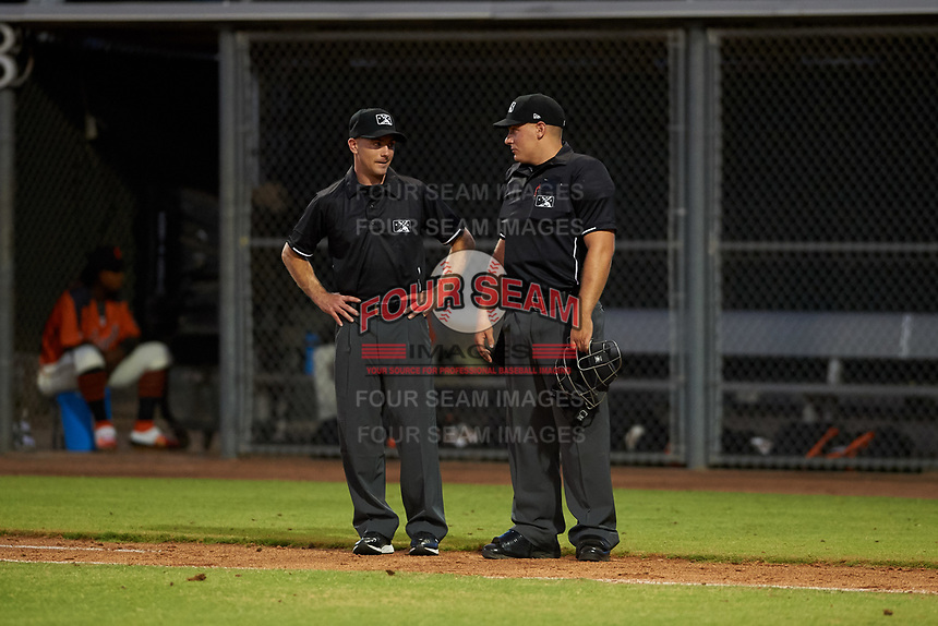 Umpires Josh Williams and Luke Morris talk between innings of a game between the AZL Angels and AZL Giants Orange at Giants Baseball Complex on June 17, 2019 in Scottsdale, Arizona. AZL Giants Orange defeated AZL Angels 8-4. (Zachary Lucy/Four Seam Images)