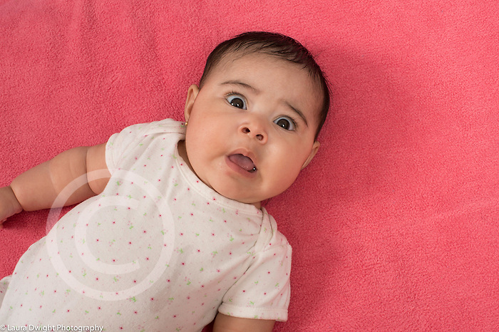 4 month old baby girl lying on back shocked, surprised  expression