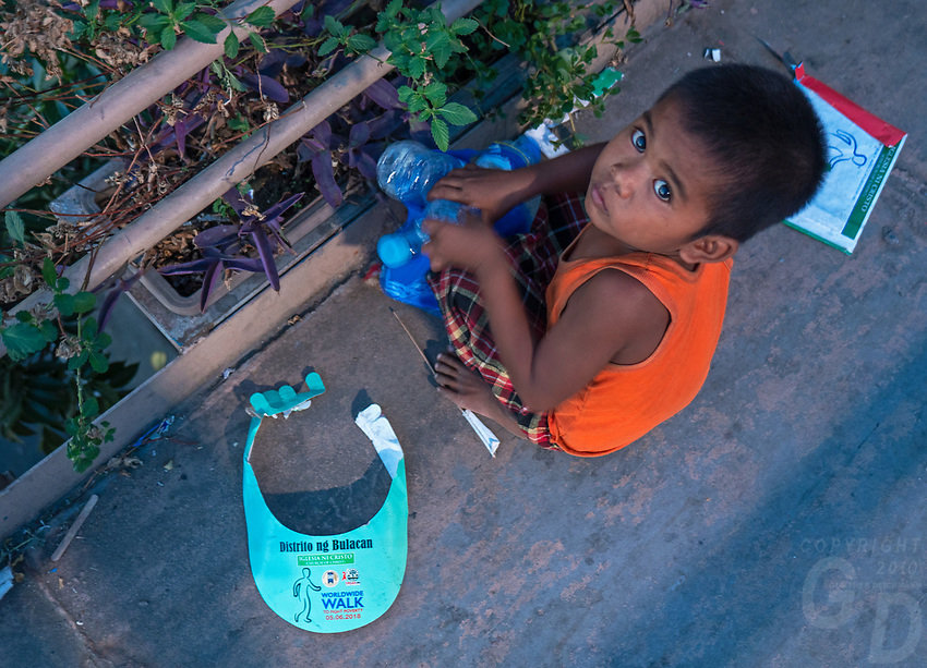 Rubbish on the streets of Manila after the World Poverty Day, Philippines A young Boy collecting Plastic Bottles