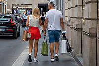 Milan, Italy , july 3 2021 - first day of summer sales - couple walking with bags in Montenapoleone street