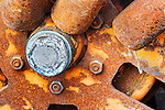 Rusted, vintage, antique, wheel hub in salvage  yard.  Spokes, bolts, and bearings.