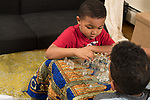 5 year old boy playing chess game with 10 year old brother, older brother coaching him on moves