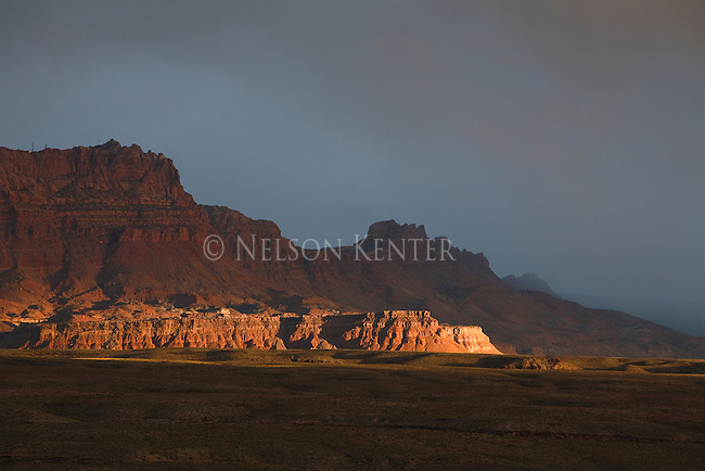 Sun spotlights the lower rock ridge in the valley near Canyon Ferry in Arizona during a late day thunderstorm